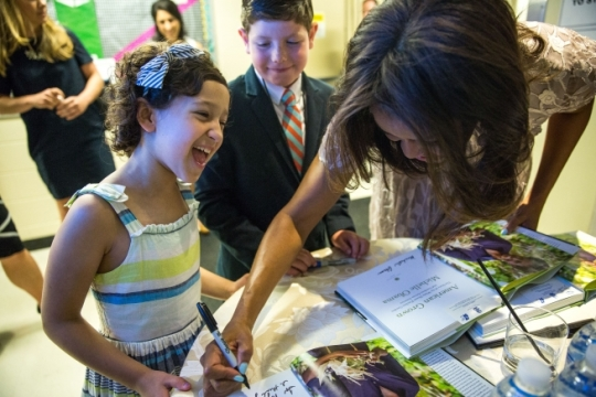 Rylie Richards and Paul Baier watch First Lady Michelle Obama sign autographs after the Woodmark Children's Forum luncheon in Washington, D.C., June 11, 2015. Rylie introduced the First Lady for remarks during the forum. (Official White House Photo by Amanda Lucidon)