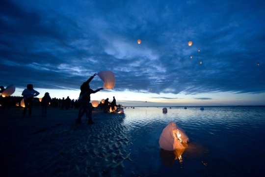 Local residents of the Normandy, France, region, release paper sky lanterns June 5, 2015, to commemorate those who died here on D-Day, at a place the Allied Forces named Utah Beach for the invasion of an occupied France, 71 years ago. More than 380 American service members from Europe and affiliated D-Day historical units are participating in the 71st anniversary as part of Joint Task Force D-Day 71, June 2-8, 2015.