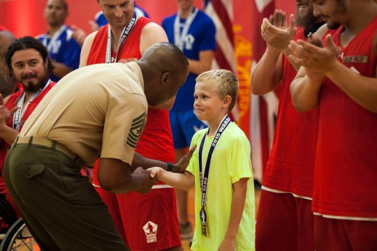U.S. Marine Corps veteran Clayton McDaniels' son receives a gold medal on behalf of his father who won the wheelchair basketball championship game at Marine Corps Base (MCB) Quantico, Va., June 18, 2015. McDaniels is a member of the 2015 Department of Defense (DoD) Warrior Games All-Marine Team. The 2015 DoD Warrior Games, held at MCB Quantico June 19-28, is an adaptive sports competition for wounded, ill, and injured Service members and veterans from the U.S. Army, Marine Corps, Navy, Air Force, Special Operations Command, and the British Armed Forces. (U.S. Marine Corps photo by Cpl. Ashley Cano/Released)