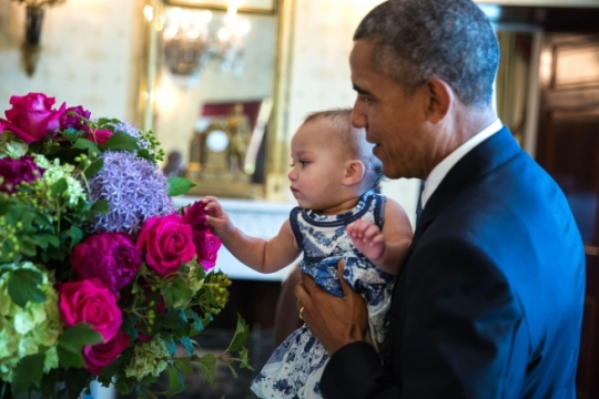 President Barack Obama shows Soleil Malveaux Jean-Pierre a floral arrangement in the Blue Room of the White House prior to a reception to observe LGBT Pride Month in the East Room, June 24, 2015. (Official White House Photo by Pete Souza)