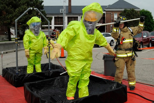 Emergency personnel receive a scrub down during a training exercise at Selfridge Air National Guard Base, Mich., June 5, 2015. During the exercise, a smoke machine was used to create a simulated cloud of chlorine gas after an industrial accident. Firefighters and other base personnel trained in the steps necessary to respond to such an emergency. Airmen at Selfridge conduct a variety of training exercises every year to be able to respond to local emergencies and/or to deploy to forward locations. (U.S. Air National Guard photo by Terry Atwell)