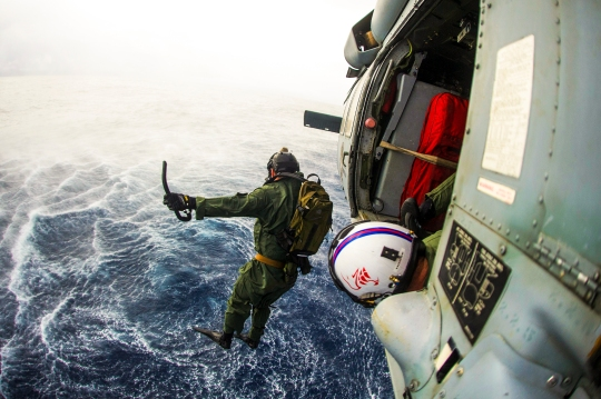 150618-N-EH855-673  CORAL SEA (June 18, 2015) A member of Explosive Ordnance Disposal Mobile Unit (EODMU) 5, embarked aboard the Nimitz-class aircraft carrier USS George Washington (CVN 73), jumps from an MH-60S Sea Hawk helicopter from the Golden Falcons of Helicopter Sea Combat Squadron (HSC) 12 during a floating mine response drill. George Washington and its embarked air wing, Carrier Air Wing (CVW) 5, are on patrol in the U.S. 7th Fleet area of responsibility supporting security and stability in the Indo-Asia-Pacific region. George Washington will conduct a hull-swap with the Nimitz-class aircraft carrier USS Ronald Reagan (CVN 76) later this year after serving seven years as the U.S. Navy's only forward-deployed aircraft carrier in Yokosuka, Japan. (U.S. Navy photo by Mass Communication Specialist 3rd Class Bryan Mai/Released)