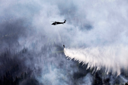 "An Alaska Army National Guard UH-60 Black Hawk helicopter from 1st Battalion, 207th Aviation Regiment, drops approximately 700 gallons of water from a ""Bambi Bucket"" on to the Stetson Creek Fire near Cooper Landing, Alaska, June 17. Two AKARNG Black Hawk helicopters flew a total of 200 bucket missions, dumping more than 144,000 gallons of water on the 300-acre Stetson Creek Fire on the Kenai Peninsula. (U.S. Army National Guard photo by Sgt. Balinda O'Neal)"