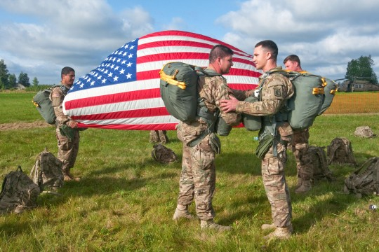Sgt. Sean Fitzgibbons, (right) of North Attleboro, Massachusetts, an intelligence analyst with Headquarters and Headquarters Company, 2nd Battalion, 503rd Infantry Regiment, 173rd Airborne Brigade Combat Team re-enlists prior to a joint airborne jump conducted July 23, at a drop zone in Nurmsi, Estonia. Throughout the day, Fitzgibbons along with his U.S. and Estonian comrades took their turn entering and jumping from a UH 60 Black Hawk helicopter. (U.S. Army Photo by Sgt. Juana M. Nesbitt, 13th Public Affairs Detachment)