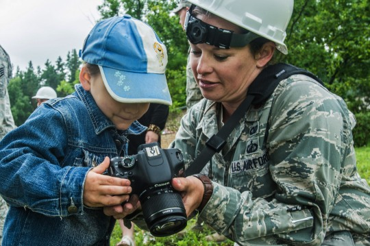 U.S. Air Force Maj. Melanie Englert (right), public affairs officer with the 139th Airlift Wing, Missouri Air National Guard, shows a Latvian orphan her camera during the reconstruction of the Naujenu Orphanage near Daugavpils, Latvia, July 20, 2015. Airmen from the 139th Civil Engineer Squadron, Missouri Air National Guard, were participating in a Humanitarian Civic Assistance project that pairs units training requirements with humanitarian needs.  (U.S. Air Force photo by Senior Airman Patrick P. Evenson/Released)