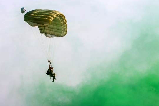 A U.S. Air Force Pararescueman with a Guardian Angel team assigned to the 83rd Expeditionary Rescue Squadron parachutes to the ground during High Altitude Low Opening jump training at Bagram Air Field, Afghanistan, July 18, 2015. To mark the drop zone, green smoke was used to guide the Pararescuemen to their landing point. The 83rd ERQS mission is to rescue, recover, and return American or allied forces in times of danger or extreme duress. (U.S. Air Force photo by Tech. Sgt. Joseph Swafford/Released)
