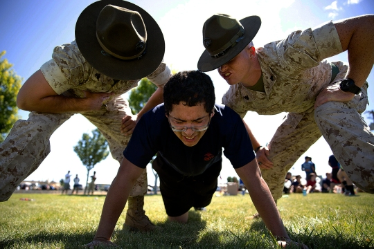 Sgts. Stephen Wills (left) and Brandon Hendrix, drill instructors from Marine Corps Recruit Depot San Diego, motivate Jose Garcia, a Marine enlistee from Yakima, Wash., during a Recruiting Station Seattle pool function at the Yakima Training Center in Yakima, July 17, 2015. During the event, recruiters teamed with drill instructors to physically and mentally prepare enlistees from Washington and Idaho for boot camp. The enlistees, part of the Marine Corps delayed entry program, are awaiting their ship dates. Wills, 24, is from Phoenix and is assigned to Echo Company, 2nd Recruit Training Battalion. Hendrix, 26, is from Redlands, Calif., and is assigned to Lima Company, 3rd Recruit Training Battalion. Garcia, 17, is set to become a senior at Eisenhower High School in Yakima and was recruited by Sgt. James Campos. (U.S Marine Corps photo by Sgt. Reece Lodder)
