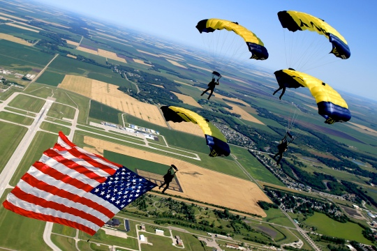 150725-N-ZZ999-007  Fargo, N.D. (July 26, 2015) Members of the U.S. Navy Parachute Team, the Leap Frogs, perform a diamond while flying the American flag during a demonstration at the Fargo Air Show. The Leap Frogs are based in San Diego and perform aerial parachute demonstrations around the nation in support of naval special warfare and Navy recruiting. (U.S. Navy photo by Jim Woods/Released)