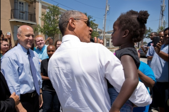 President Barack Obama greets a youngster during a walk through the Tremé neighborhood of New Orelans, La., with Mayor Mitch Landrieu, left, Aug. 27, 2015. The area experienced significant flooding during Hurricane Katrina ten years ago. (Official White House Photo by Pete Souza)