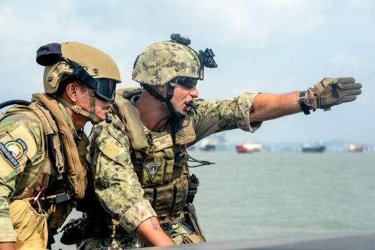 """150807-N-FN215-085 SURABAYA, Indonesia (Aug. 7, 2015) Boatswain's Mate 1st Class Kevin Diebold,  right, assigned to Coastal Riverine Squadron (CRS) 3, communicates with an Indonesian """"Kopaska"""" Naval Special Forces team leader while practicing interdiction techniques during Cooperation Afloat Readiness and Training (CARAT) Indonesia 2015. In its 21st year, CARAT is an annual, bilateral exercise series with the U.S. Navy, U.S. Marine Corps and the armed forces of nine partner nations. (U.S. Navy photo by Mass Communication Specialist 1st Class Joshua Scott/Released)"""