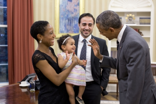 President Barack Obama greets Alya Dorelien Bitar, the one-year-old daughter of Maher Bitar, the outgoing National Security Council Director for Israeli and Palestinian Affairs, and his wife, Astrid Dorelien, during a family photo in the Oval Office, Sept. 21, 2015. (Official White House Photo by Pete Souza)