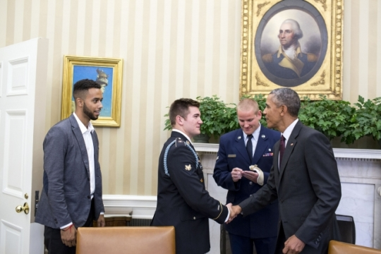 President Barack Obama welcomes, from left, Anthony Sadler, U.S. Army Specialist Alek Skarlatos and U.S. Air Force Airman 1st Class Spencer Stone to the Oval Office while handing them each a Presidential Challenge Coin, Sept. 17, 2015. The President expressed his gratitude to the three Americans for their selfless actions and extraordinary bravery on Aug. 21, 2015, while subduing a gunman on a train traveling from Amsterdam to Paris. (Official White House Photo by Pete Souza)