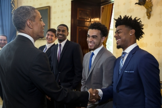 President Barack Obama talks with Duke University Blue Devils men's basketball players, from right, Quinn Cook, Tyus Jones, Matt Jones and Grayson Allen during a greet with the team, coaches and University leadership prior to an event to honor the team and their 2015 NCAA Championship victory, in the Blue Room of the White House, Sept. 8, 2015. Head Coach Mike Krzyzewski, background, watches the exchange. (Official White House Photo by Pete Souza)