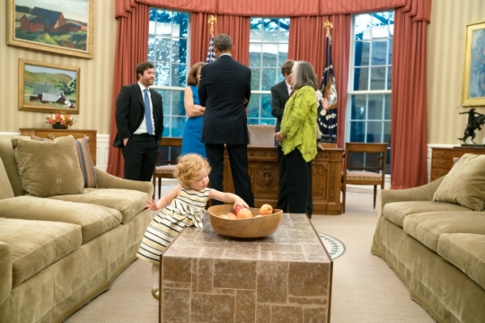 Twenty-one-month-old Lillian McNally reaches for an apple as President Barack Obama visits with her mother, Amanda Anderson, Office of Legislative Affairs and father Matthew McNally, left. in the Oval Office, Oct. 8, 2015. Also attending Amanda's departure ceremony are her parents, William and Catherine Anderson and Logan Anderson, her three-year-old nephew. (Official White House Photo by Pete Souza)