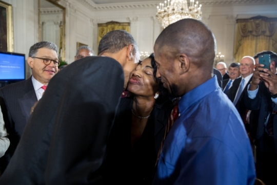 President Barack Obama gets a kiss from Joann Wise, the mother of Terrence Wise, right, who earlier introduced the President for remarks at the White House Summit on Worker Voice in the East Room, Oct. 7, 2015. Terrance Wise, a second generation Kansas City fast food worker making $8 an hour at two jobs, is an organizer with Fight for $15, a movement dedicated to winning workers a $15 minimum wage and the right to unionize. (Official White House Photo by Pete Souza)
