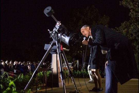 "President Barack Obama looks at the moon through a telescope while talking with student Agatha Sofia ""Sofy"" Alvarez Bareiro during the White House Astronomy Night on the South Lawn of the White House, Oct. 19, 2015. (Official White House Photo by Pete Souza)"