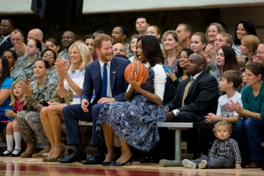 First Lady Michelle Obama and Dr. Jill Biden react after Prince Harry of Wales hands the First Lady a ball that came to him while watching a wheelchair basketball game in the field house at Fort Belvoir, Va., Oct. 28, 2015. Their visit to Fort Belvoir is in support of the Joining Forces initiative and the Invictus Games. (Official White House Photo by Chuck Kennedy)