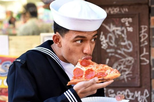 Navy Seaman Kevin Carranza enjoys a slice of pizza while participating in Veterans Day events in New York City, Nov. 9, 2015. Carranza is a hospitalman apprentice assigned to the USS New York. U.S. Navy photo by Petty Officer 1st Class Brian McNeal