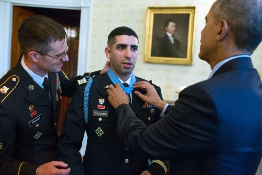 President Barack Obama, with Sergeant Andrew Mahoney, adjusts the Medal of Honor on Captain Florent A. Groberg, U.S. Army (Ret), in the Blue Room of the White House following the Medal of Honor ceremony, Nov. 12, 2015. Captain Groberg received the Medal of Honor for his courageous actions while serving as a Personal Security Detachment Commander for Task Force Mountain Warrior, 4th Infantry Brigade Combat Team, 4th Infantry Division during combat operations in Asadabad, Kunar Province, Afghanistan on August 8, 2012. (Official White House Photo by Pete Souza)