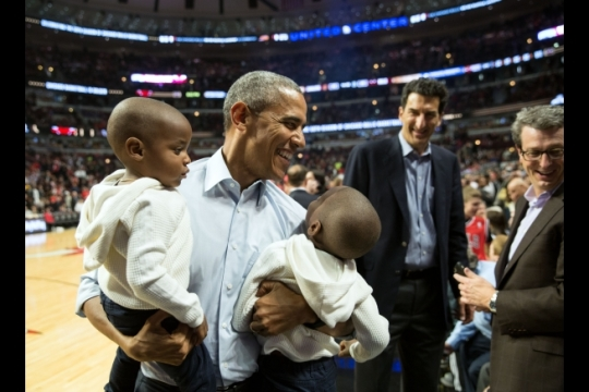President Barack Obama holds two youngsters while posing for a photo with them during halftime of the Chicago Bulls-Cleveland Cavaliers basketball game at the United Center in Chicago, Ill., Oct. 27, 2015. (Official White House Photo by Pete Souza)