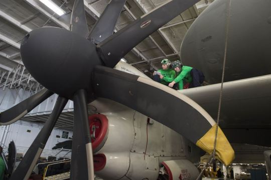 Navy Petty Officer 1st Class Christopher Marsh, left, and Petty Officer 3rd Class Phillip Botts conduct a corrosion inspection on an E-2C Hawkeye in the hangar bay of the USS Dwight D. Eisenhower in the Atlantic Ocean, Nov. 25, 2015. Marsh is an aviation structural mechanic and Botts is an aviation electronics technician. The aircraft is assigned to Airborne Early Warning Squadron 123. U.S. Navy photo by Petty Officer Seaman Anderson W. Branch