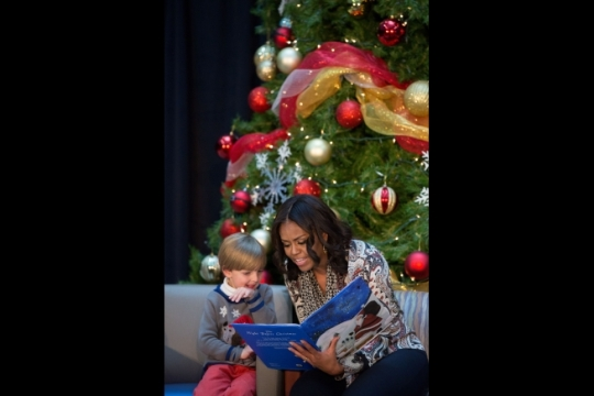 """First Lady Michelle Obama reads """"'Twas the Night Before Christmas"""" with six-year-old elf Stephen Orzechowski during a Christmas holiday program at the Children's National Medical Center in Washington, D.C., Dec. 14, 2015. (Official White House Photo by Amanda Lucidon)"""