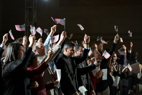Newly naturalized citizens wave American flags after taking the Oath of Allegiance during a naturalization ceremony at the National Archives in Washington, D.C., Dec. 15, 2015. (Official White House Photo by Pete Souza)