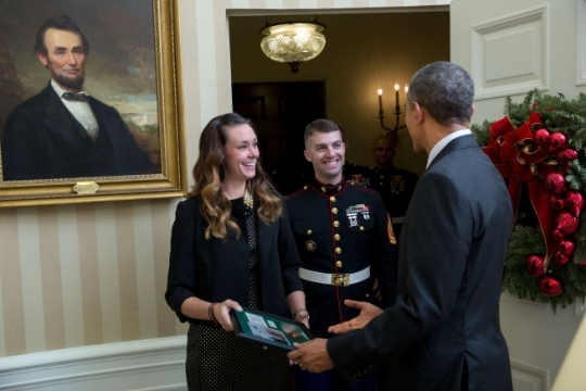 President Barack Obama receives a framed copy of the Marine Helicopter Squadron One (HMX-1) Christmas holiday greeting card from Erin Strohschein and Gunnery Sergeant Christopher Strohschein in the Oval Office, Dec. 8, 2015. (Official White House Photo by Lawrence Jackson)