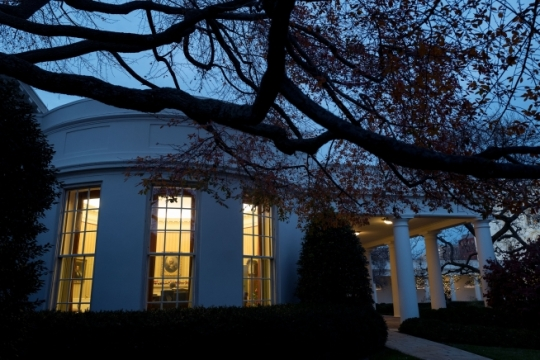 President Barack Obama works in the Oval Office at dusk as seen from the South Lawn of the White House, Dec. 7, 2015. (Official White House Photo by Pete Souza)