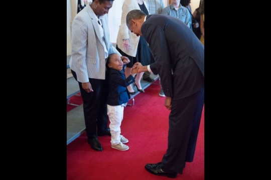 President Barack Obama greets Armanii Chisholm, age 3, as his grandmother, Chief Religious Program Specialist Tameca Brown, looks on during a tour with wounded warriors and their families in the Cross Hall of the White House, July 25, 2016. (Official White House Photo by Pete Souza)