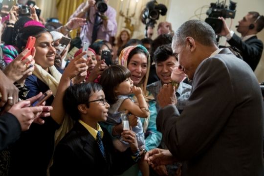 President Barack Obama smells a rose given to him by Sophia Ahmadi, 2, as her parents, Zainab Ahmadi and Mohammad Ahmadi, look on during the Eid al-Fitr reception in the East Room of the White House, July 21, 2016. (Official White House Photo by Pete Souza)