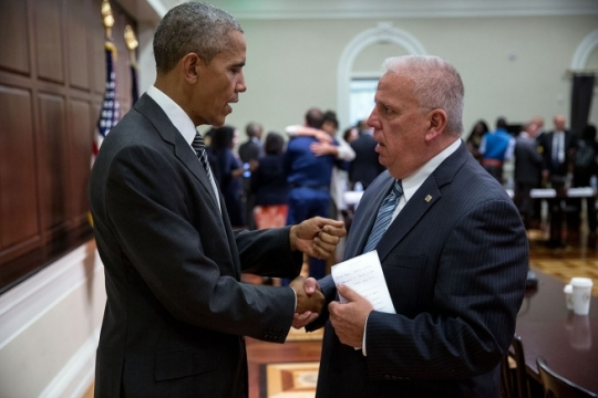 President Barack Obama talks with Mick McHale, President, National Association of Police Organizations, after meeting with activists, civil rights, faith, law enforcement and elected leaders on building community trust, in the Eisenhower Executive Office Building of the White House, July 13, 2016. In the background, Black Lives Matter activist Mica Grimm hugs Col. Michael D. Edmonson, Superintendent of Police, Louisiana State Police. (Official White House Photo by Pete Souza)