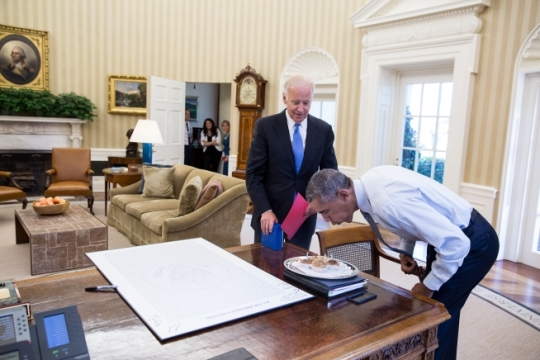 President Barack Obama blows out candles on birthday cupcakes brought to him by Vice President Joe Biden in the Oval Office, Aug. 4, 2016. (Official White House Photo by Pete Souza)