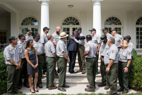 President Barack Obama hugs Ed Thomas, a White House groundskeeper with the National Park Service for 43 years, following a group photo with members of the White House National Park Service team in the Rose Garden, Aug. 25, 2016. The National Park Service is celebrating its 100th anniversary. (Official White House Photo by Amanda Lucidon)