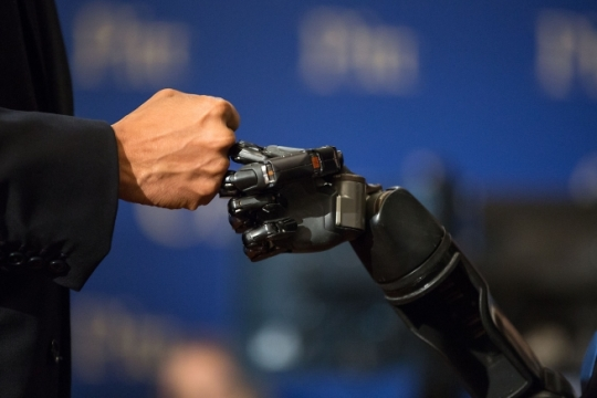 President Barack Obama fist-bumps the robotic arm of Nathan Copeland during a tour at the White House Frontiers Conference at the University of Pittsburgh in Pittsburgh, Pa., Oct. 13, 2016. For the first time ever in humans a technology that allowed Copeland to experience the sensation of touch through a robotic arm that he controls with his brain. (Official White House Photo by Pete Souza)