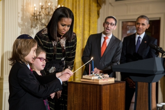 President Barack Obama, First Lady Michelle Obama and Rabbi Steven Exler watch Elijah and Shira Wiesel light the menorah during a Hanukkah reception in the East Room of the White House, Dec. 14, 2016. (Official White House Photo by Chuck Kennedy) 3 of 10